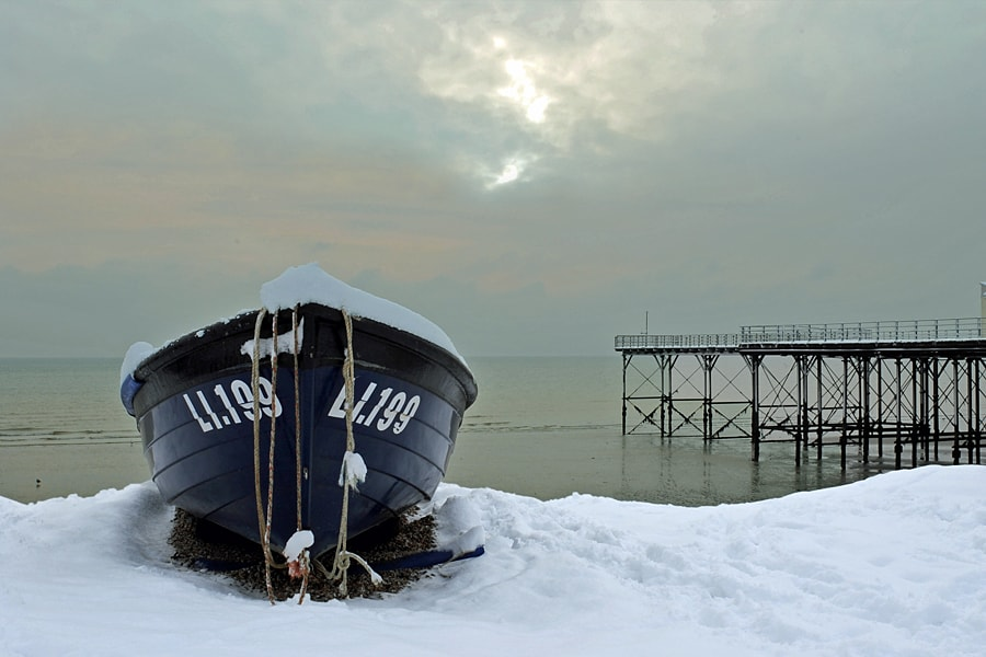 Fishing boat in the snow on the beach at Bognor Regis, West Sussex